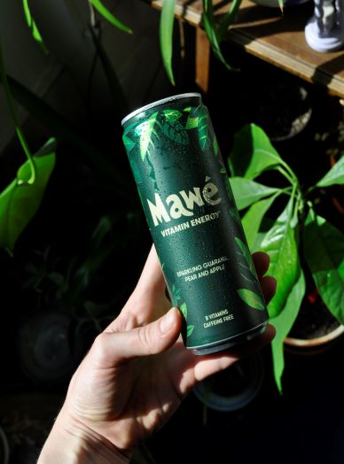 Hand holding a can of Mawé