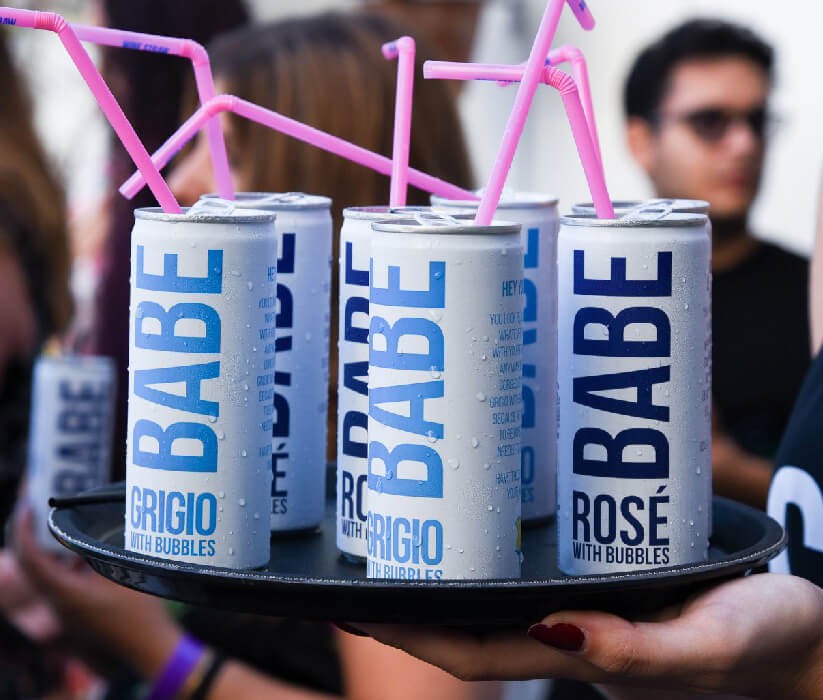 Multiple cans of Babe canned wine on a serving tray with pink straws